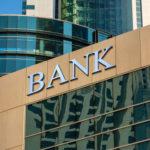 """Ein Bildausschnitt eines Gebäudes mit Glasfassade und der Aufschrift """"Bank"""""""