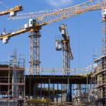 Baulandschaft mit Kränen und neu zu errichtenden Wohnungen