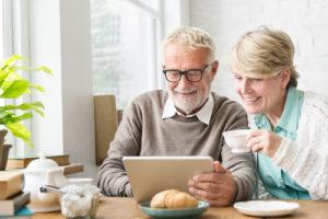 Ein Seniorenpaar sitzt am Frühstückstisch und schaut lächelnd auf ein Tablet