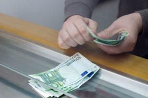 Ein Mann zählt Geldscheine am Bankschalter ab