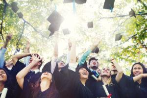 Studenten feiern ihren Abschluss und werfen ihre Hüte in die Luft