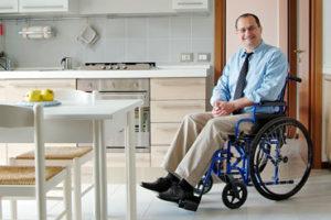 Ein Mann mit Krawatte im Rollstuhl in seiner Wohnküche