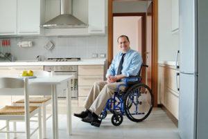 Ein fröhlicher Mann mit Krawatte im Rollstuhl in seinem Esszimmer