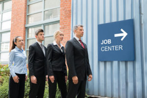Drei Männer im Anzug und eine Frau im Kostüm vor einem Schild zum Job Center