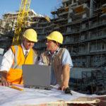 Zwei Männer mit Bauhelmen stehen vor Rohbauten an einem Tisch mit Bauplänen und einem Laptop
