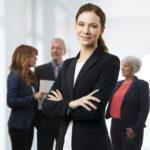 Junge Anwältin im Vordergrund und drei Personen im Hintergrund