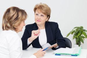 Eine Frau mittleren Alters berät eine andere und zeigt etwas auf einem Tablet Computer