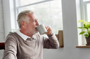 Ein älterer Herr sitzt am Fenster, schaut hinaus und trinkt einen Kaffee
