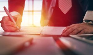 Ein Mann im Anzug steht an einenm Schreibtisch und schreibt etwas auf ein Dokument