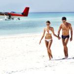 Ein Paar am Sandstrand mit Wasserflugzeug im Hintergrund