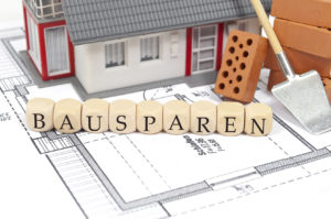 Auf einem Bauplan steht ein Spielzeughaus und Buchstabenwürfel, die das Wort Bausparen bilden