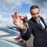 Ein gelackter Autohändler im Anzug streckt einen Autoschlüssel entgegen