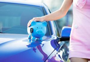 Eine Frau im rosa Kleid steht neben einem Neuwagen auf dem ein Sparschwein steht, auf das sie ihre Hand legt