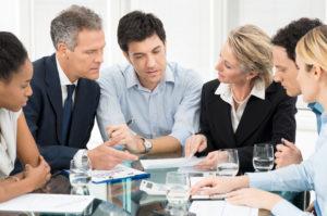 Mehrere Personen im Business Outfit besprechen sich an einem großen Glastisch