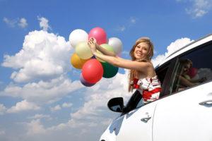 Eine lachende Frau lehnt sich aus einem Autofenster und hält dabei viele bunte Luftballons in den Händen