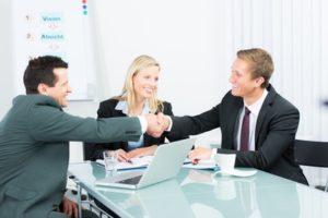 Zwei Männer im Anzug sitzen an einem Tisch auf dem Unterlagen liegen und geben sich die Hand