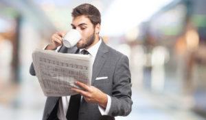 Junger Mann mit Anzug trinkt eine Tassee Kaffee und liest die neueste Zeitung