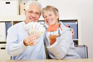 Ein glückliches älteres Paar halten ein Spielzeughaus und einige Euroscheine hoch
