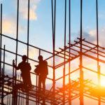 Zwei Bauarbeiter auf einem Baugerüst bei Sonnenuntergang