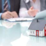 Auf einem Glastisch steht das Modell eines Hauses, im Hintergrund verhandeln zwei Menschen