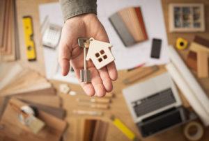 Auf einer geöffneten Hand liegt ein Hausschlüssel und eine Schlüsselanhänger aus Holz