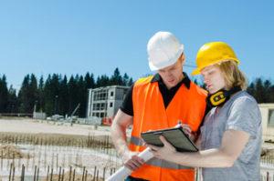 Zwei junge Männer mit Bauhelmen und einem Tablet Computer vor einer Baustelle