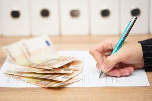 Jemand unterschreibt einen Vertrag auf dem einige fünfzig Euro Scheine liegen