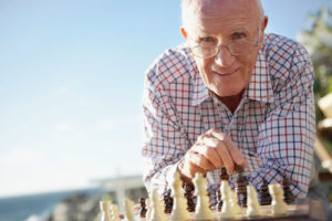 Ein alte rMann sitzt lächelnd an einem Schachbrett und bewegt eine Figur