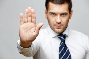 Ein Mann mit Krawatte hebt abwehrend eine Hand hoch