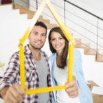 Junges Paar hält einen Zollstock in Form eines Hauses vor sich