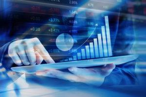 In einem Bildschirm mit Börsenkursen spiegelt sich jemand, der eine Tastatur benutzt