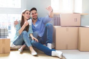 Ein glückliche junges Paar sitzt vor Umzugskisten und bespricht die Einrichtung der neuen Wohnung