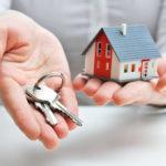 Eine Person hält ein Spielzeughaus auf offener Hand und reicht mit der anderen Hand Wohnungsschlüssel
