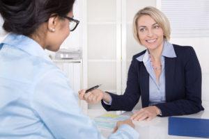 Zwei Frauen in Businesskleidung beratschlagen an einem Schreibtisch