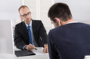 Ein Banker sitzt einem Kunden gegenüber und deutet auf eine Stelle im Vertrag,d er auf dem Tisch liegt