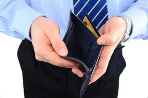 Ein Mann it Krawatte zeigt seinen offenen und leeren Geldbeutel