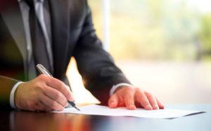 Ein Mann mit Anzug und Krawatte unterzeichnet einen Vertrag