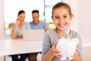 Ein Mädchen hält ein Sparschwein, in dem mehrere Geldscheine stecken