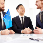 Drei Männer im Anzug am Tisch mit Statistiken und einem Europa Fähnchen