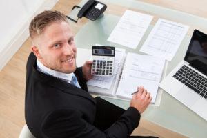 Ein freundlicher Mann im Anzug sitzt am Schreibtisch vor Unterlagen und einem Laptop und berechnet etwas mit einem Taschenrechner