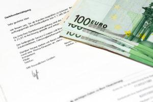 Einige hundert Euro Scheine auf einem Kreditvertrag