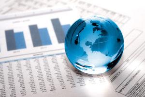 Ein gläserner Globus liegt auf Blättern mit vielen Daten und Charts