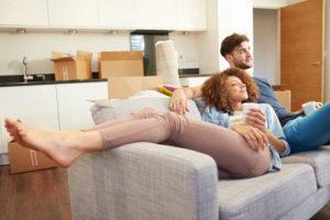 Ein junges Paar kuschelt kurz nach dem Einzug auf der Couch bei einer Tasse Kaffee