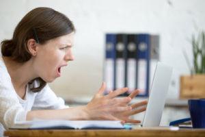 Eine junge Frau sschreit sehr verärgert ihren Laptop an