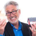 Älterer Mann hält ein Sparschwein und ein Modelhaus vor sich