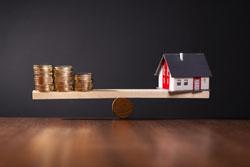 Modellhaus und Geldstapel auf Waage