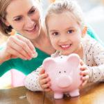 Fröhliche Mutter und Tochter füttern gemeinsam ein Sparschwein