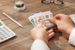 Ein Mann an einem Holztisch hält ein paar Geldscheine in der Hand. Ein Taschenrechner und ein Stift liegen auf dem Tisch