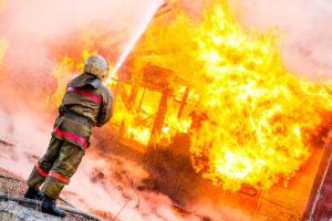 Ein Feuerwehrmann kämpft gegen die Flammen eines brennenden Hauses