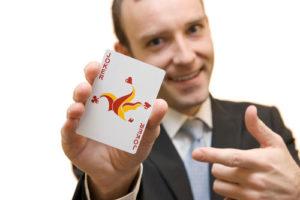Ein Mann im Anzug hält eine Joker Spielkarte vor sich